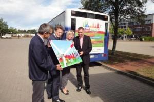 Foto vor dem Riesenplakat auf dem Bus der Stadtwerke Lübeck malt Gerd Rapior Media concept